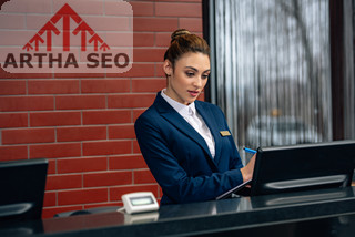 young hotel receptionist using computer at workplace